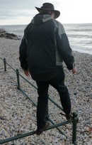 Image of a person balancing on a railing by a pebble beach