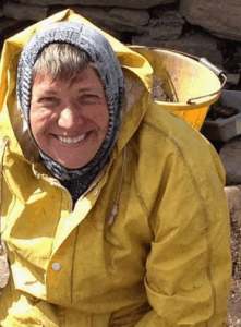 Sarah George in wet weather gear on an archaeological dig in Orkney