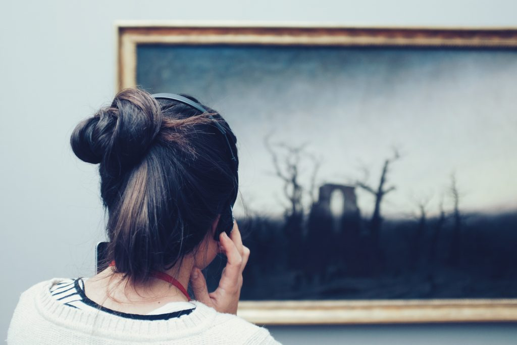 woman listening whilst looking at picture in a gallery